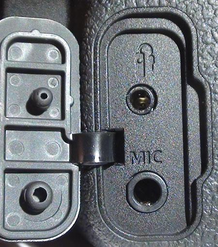 Dietro uno sportellino si trovano la presa per un microfono esterno e quella per il comando a distanza RS-60E3, che è dotato di un cavo da 60 cm e svolge interamente le funzioni del pulsante di scatto (compresa la possibilità di non scattare la foto fermandosi a metà della corsa).