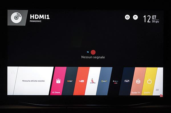 È tutto qui quanto necessario per l'uso del televisore: nella foto si vedono infatti i diversi elementi grafici raggruppati, per una migliore fruibilità, nelle due famiglie informativa e di gestione/configurazione; alla prima appartengono, ad esempio, l'icona che indica la sorgente attualmente in uso (nella foto l'ingresso HDMI 1 cui è collegato il player Blu-ray Panasonic impiegato nella prova) e l'orologio/datario. Alla seconda, invece, le già menzionate schede visibili nella parte inferiore, ma anche quella che rappresenta un ingranaggio, visibile accanto all'orologio. Il set di schede visualizzato non esaurisce però tutte le possibilità, ce ne sono altre poste a destra di quelle visibili, ed è da questa posizione che si accede ad un comodo gestore delle connessioni tramite le molte prese del pannello posteriore, oppure alla selezione dei vari possibili dispositivi (in particolare Smartphone) registrati per la condivisione di materiali audio-video.